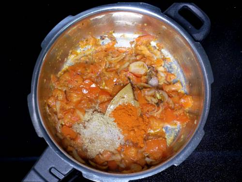 adding spice powders to make tomato rice