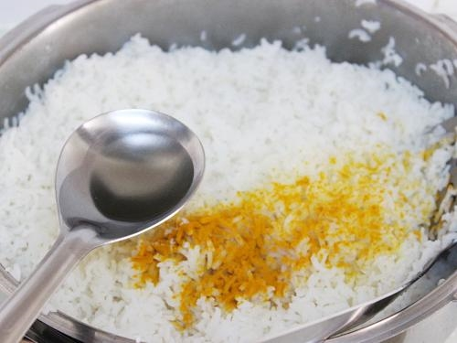 pouring oil over rice to make pulihora