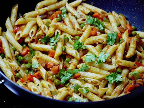 Cooked masala pasta with coriander leaves in a pan