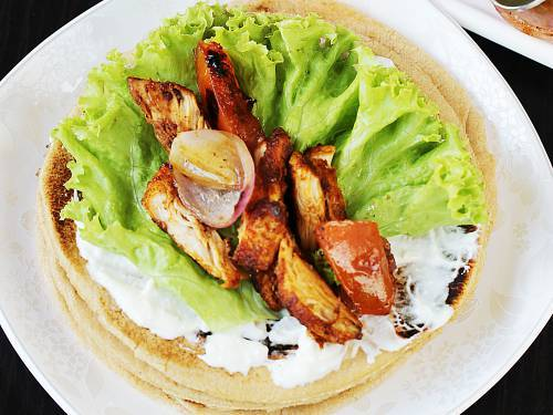 place chicken shawarma on pita bread