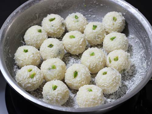 rolling coconut laddu in coconut