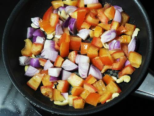 frying onions tomatoes in pan