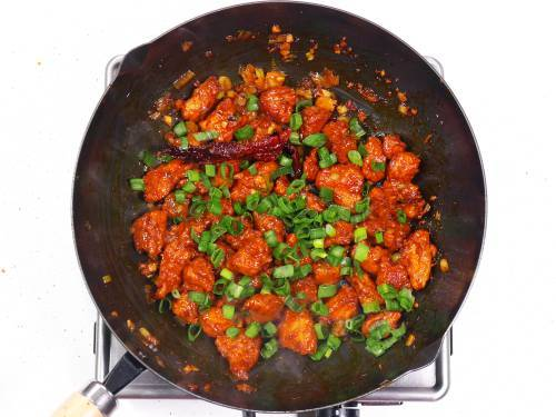garnishing szechuan chicken with spring onions