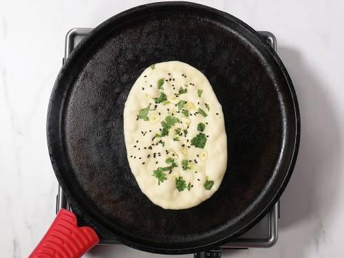 toasting garlic butter naan on cast iron skillet