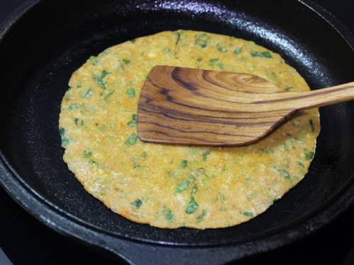 press down the vegetable paratha with a spatula