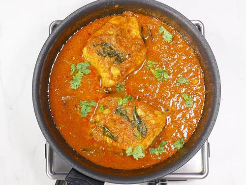 garnishing salmon curry with coriander leaves