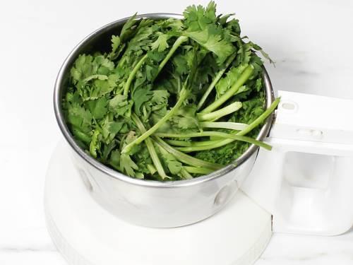 adding coriander leaves to grinder to make hara bhara kabab
