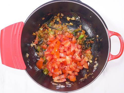 adding tomatoes to the pan