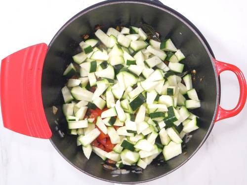 adding zucchini to the pan to make curry