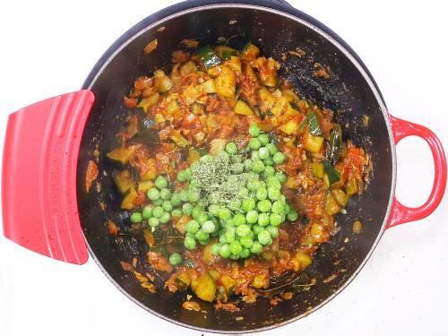 adding peas to make zucchini curry