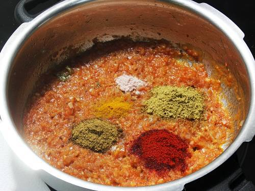 adding spice powders to make onion tomato masala