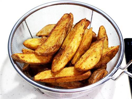 fried potato wedges in a colander ready to serve