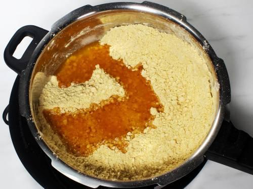 adding ghee to besan to make besan ladoo