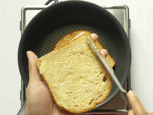 smear butter over bread to make croutons for tomato soup