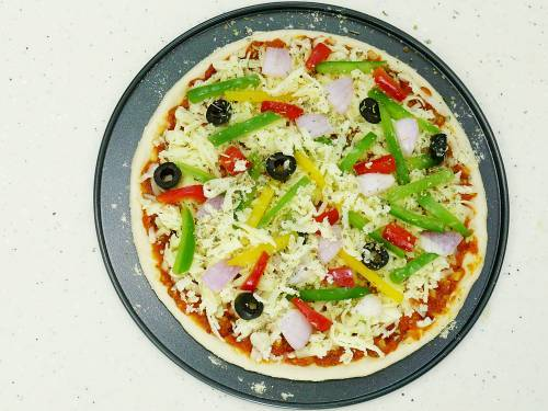 layer veggies, cheese and herbs on the pizza base
