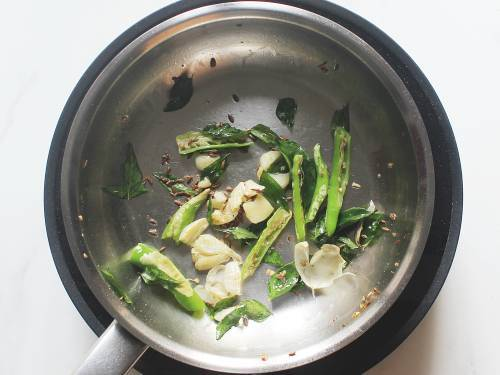 fry garlic curry leaves and chilies in pan