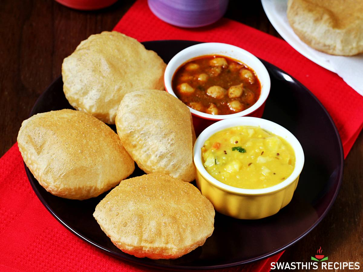 Puffed pooris served in a black plate with bhaji and spicy chana masala