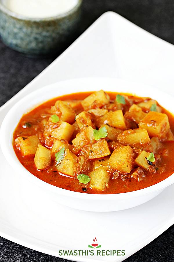 potato curry garnished with coriander leaves, served in a white bowl