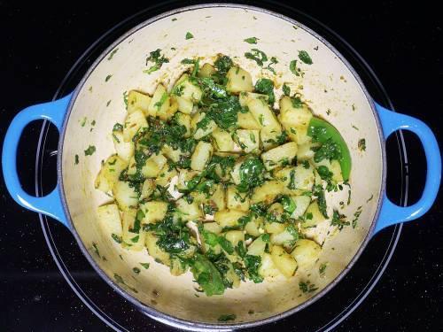 stir frying aloo and methi leaves in a pan