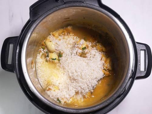add rice and  pour water to make mushroom biryani