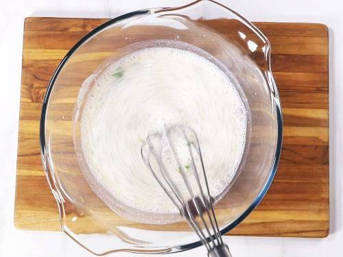 whisking chaas in a bowl until frothy