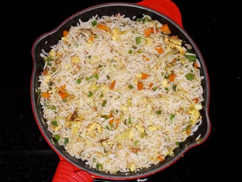 stir frying egg fried rice in a pan
