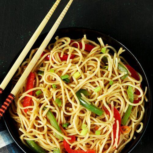 hakka noodles served in a black plate