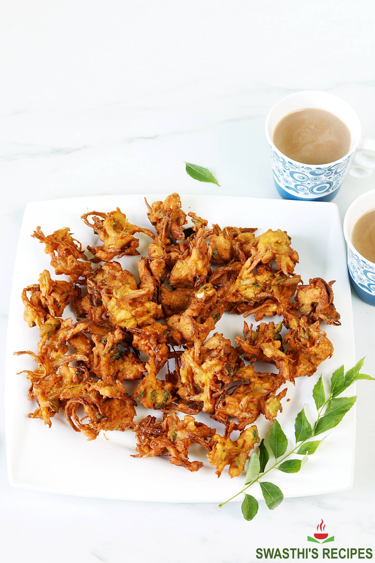 onion pakoda served in a white plate with masala tea