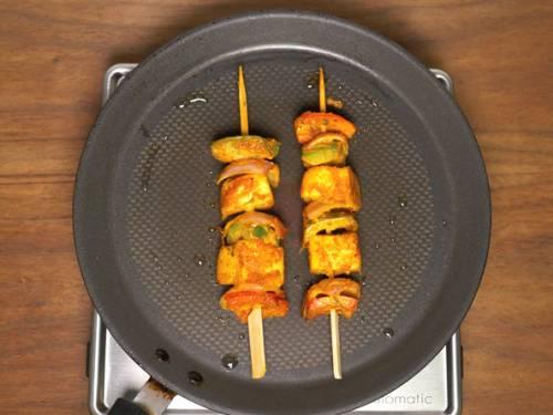 grilling paneer tikkas on a griddle